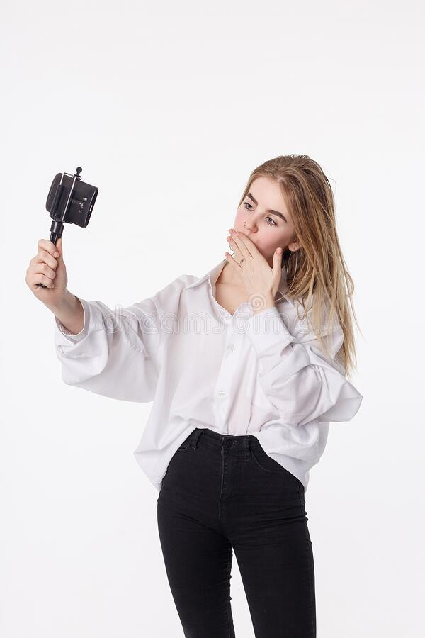 Happy young girl making self portrait with smartphone attached to small tripod royalty free stock photo