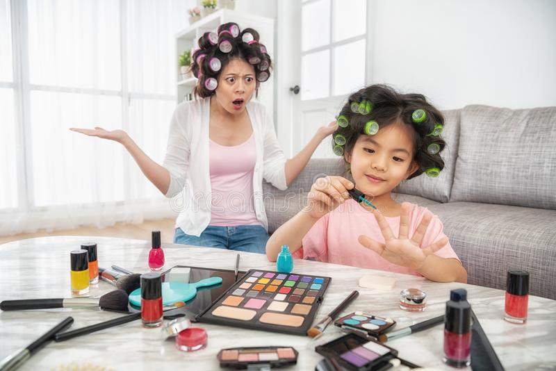Happy young girl painting her nail herself stock photo