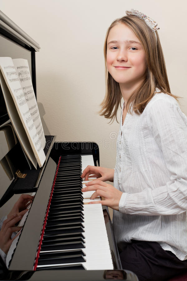 Happy young girl playing the piano royalty free stock images