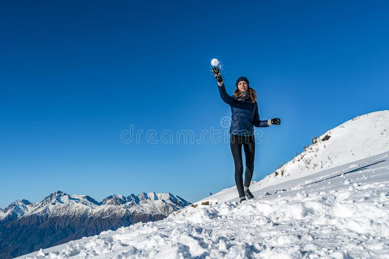 Happy young girl playing snowball fight on the winter snow day. Happy young girl playing snowball fight. friends having fun playing snowballs. Winter holidays royalty free stock image