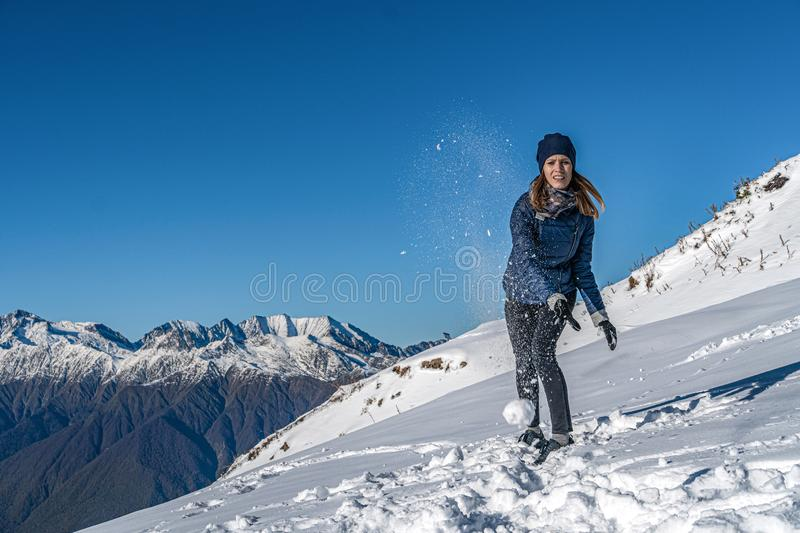 Happy young girl playing snowball fight on the winter snow day royalty free stock images