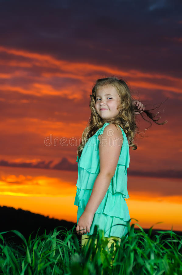 Happy young girl rest on green field