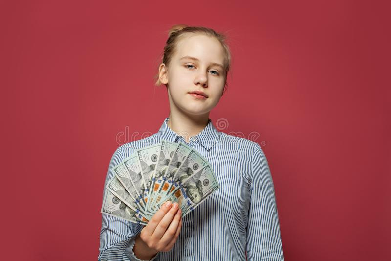 Happy young girl showing money us dollars on pink background royalty free stock photos