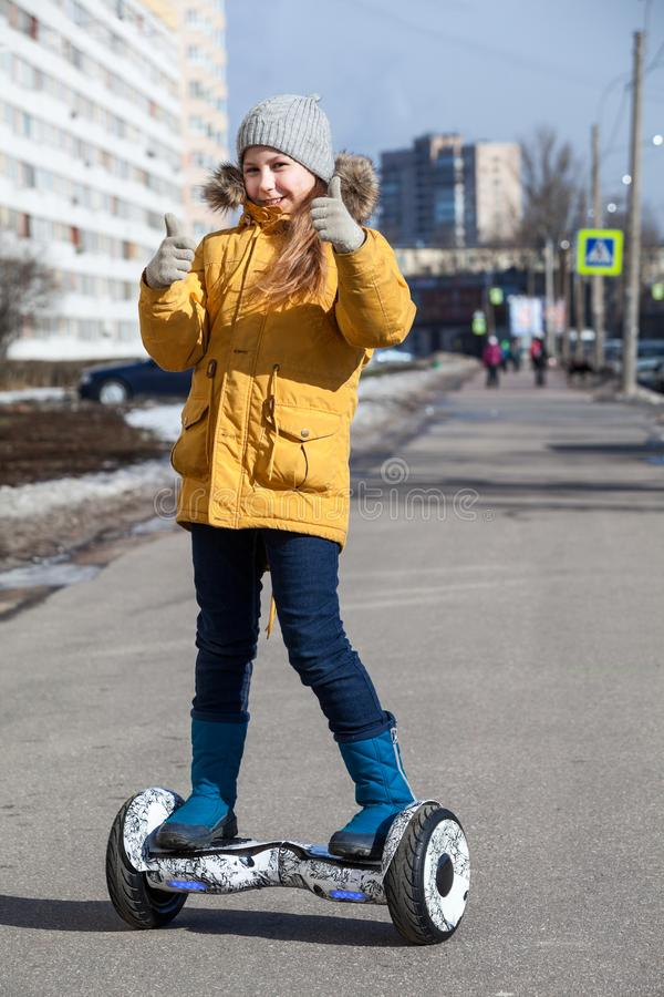 Happy young girl showing thumbs up while driving self balanced vehicle on street pathway royalty free stock photography