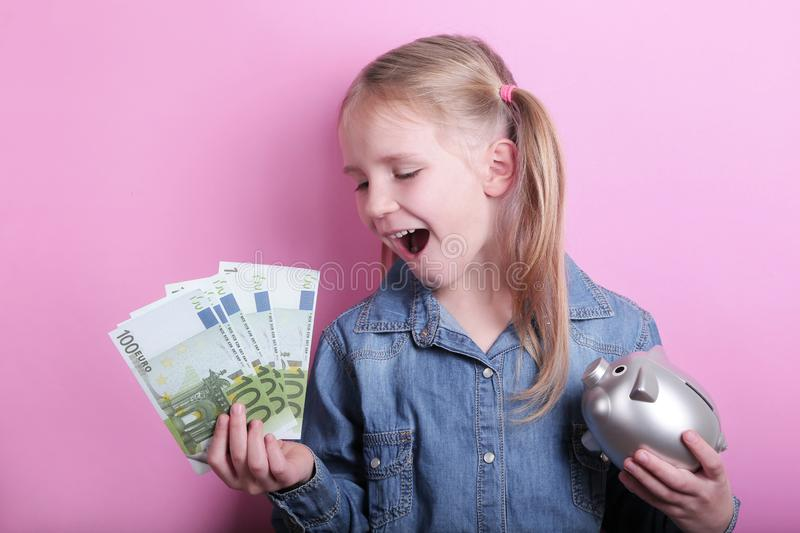 Happy young girl with silver piggy bank and euro banknotes  on pink background. save money concept. royalty free stock image