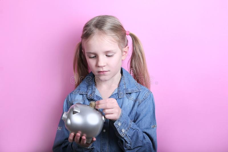 Happy young girl with silver piggy bank on pink background. save money concept. royalty free stock photography