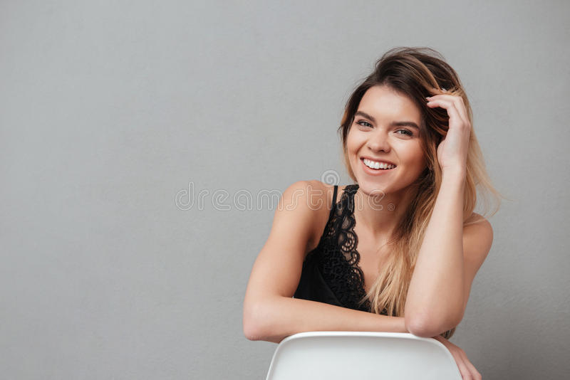 Happy young girl sitting on a chair and posing royalty free stock photography