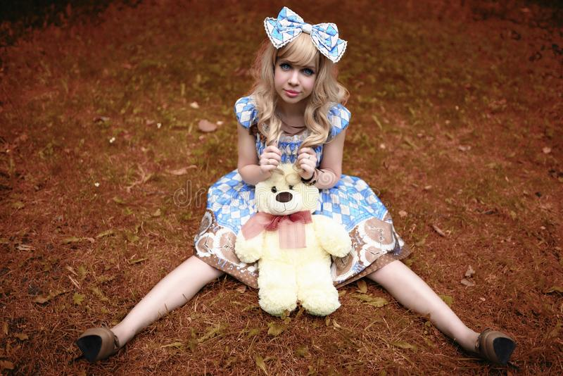 Happy young girl sitting on meadow with teddy bear in summertime dressed as doll.  royalty free stock images