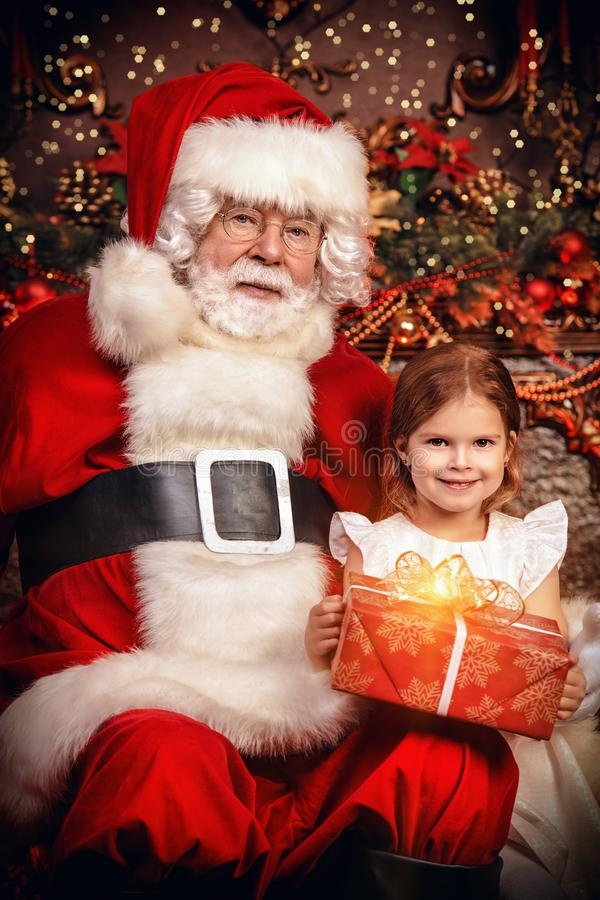 Gift box from santa. A happy young girl is sitting with a present near Santa Claus at home. Merry Christmas and Happy New Year stock photo