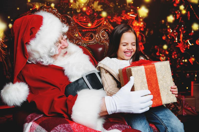 Happy girl with present. A happy young girl is sitting with a present near Santa Claus at home. Merry Christmas and Happy New Year stock photos