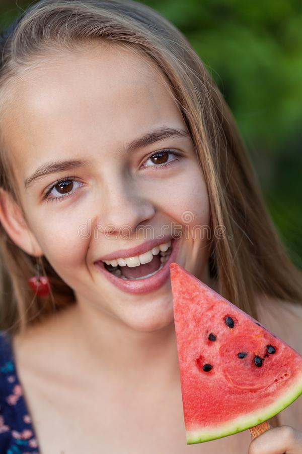 Happy young girl with a slice of watermelon on a stick stock images