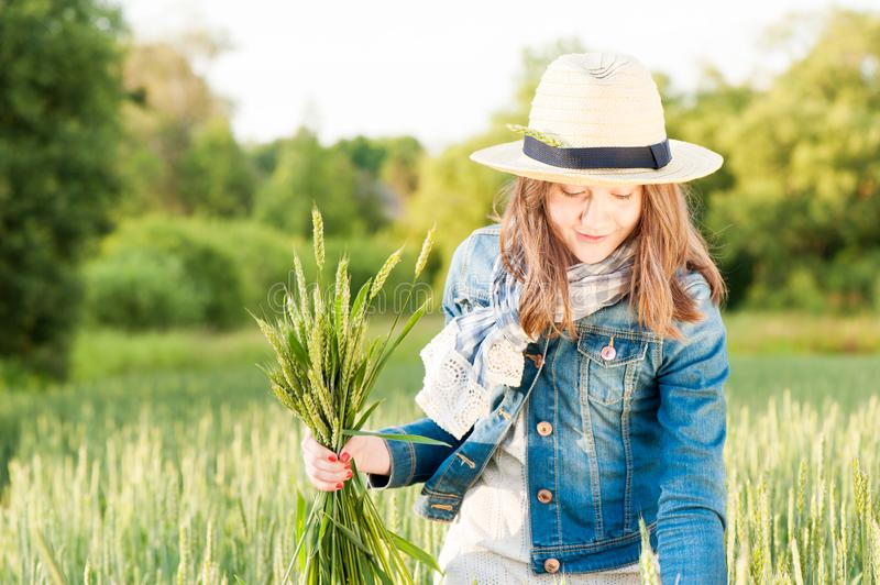 Happy young girl in summer hat picking stems on wheat field. Happy cheerful young girl in summer hat collecting stems in rays of sunlight on wheat field. Multi stock images