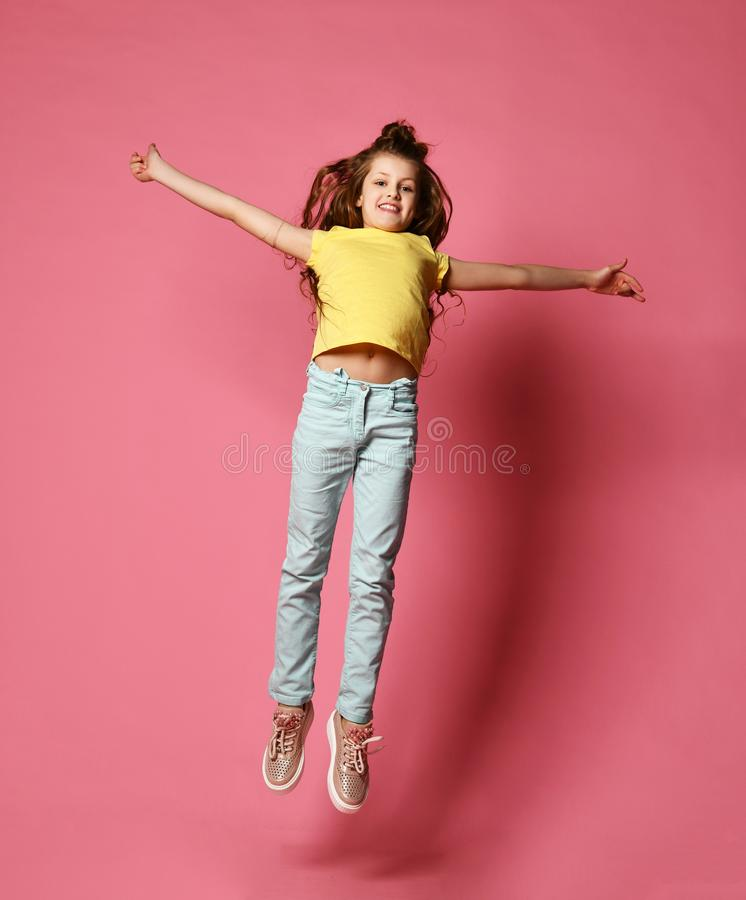 Happy young girl or teen girl in jeans and yellow t-shirt jumps high like she is flying high in skies with her arms spread royalty free stock image