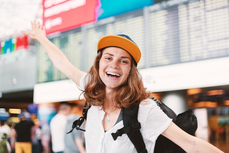 Happy young girl traveler at the airport with a backpack on the background of a departures board stock photography