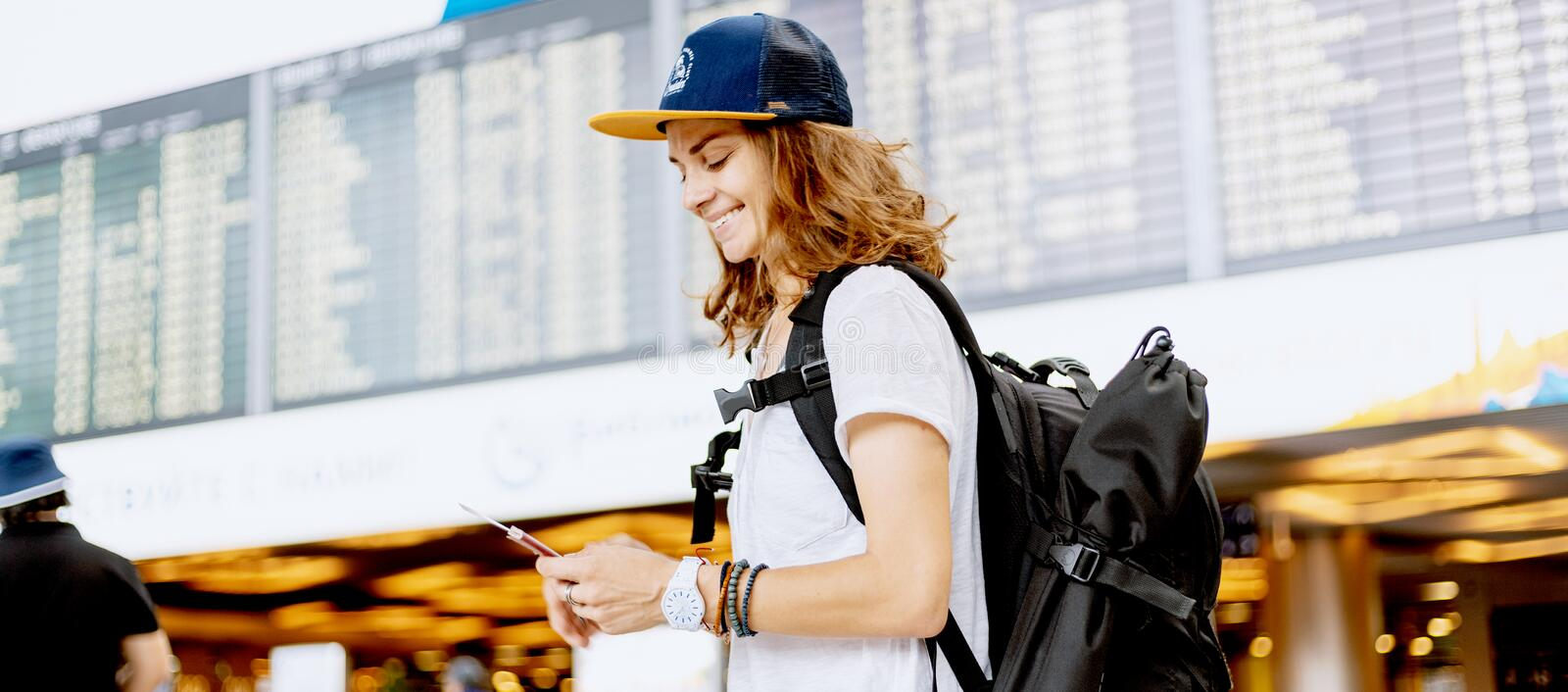 Happy young girl traveler at the airport with a backpack on the background of a departures board royalty free stock image