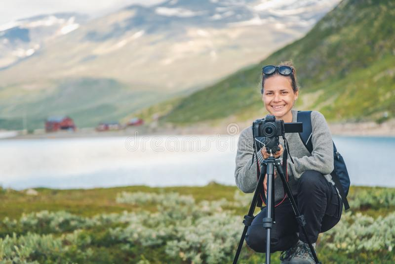 Happy young girl traveler with a camera on the background of a beautiful landscape in Jotunheimen National Park Norway stock images
