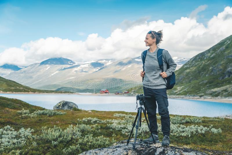 Happy young girl traveler with a camera on the background of a beautiful landscape in Jotunheimen National Park Norway royalty free stock image