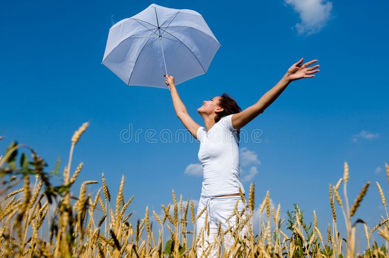 Happy young girl with umbrella in the field stock images