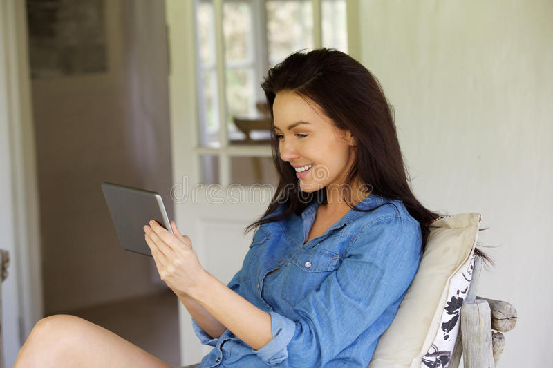 Happy young girl using digital tablet at home stock images