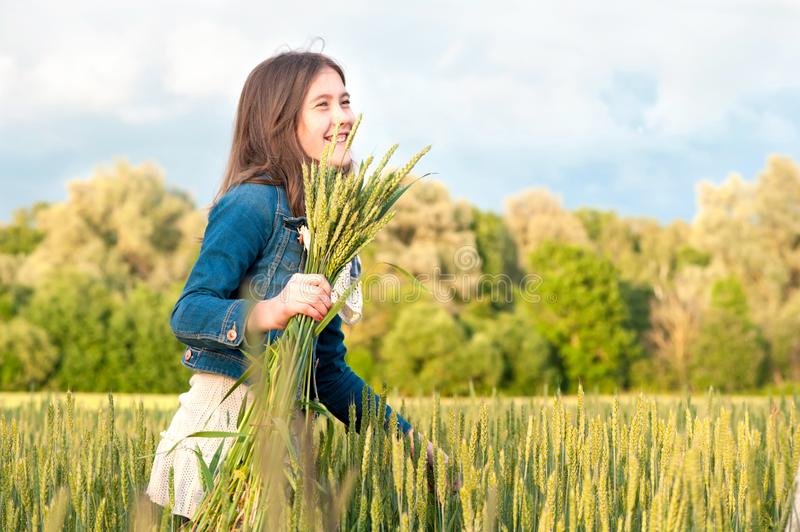 Happy young girl walking and picking stems on wheat field. Happy cheerful young girl walking and picking stems on wheat field. Summertime outdoors royalty free stock image