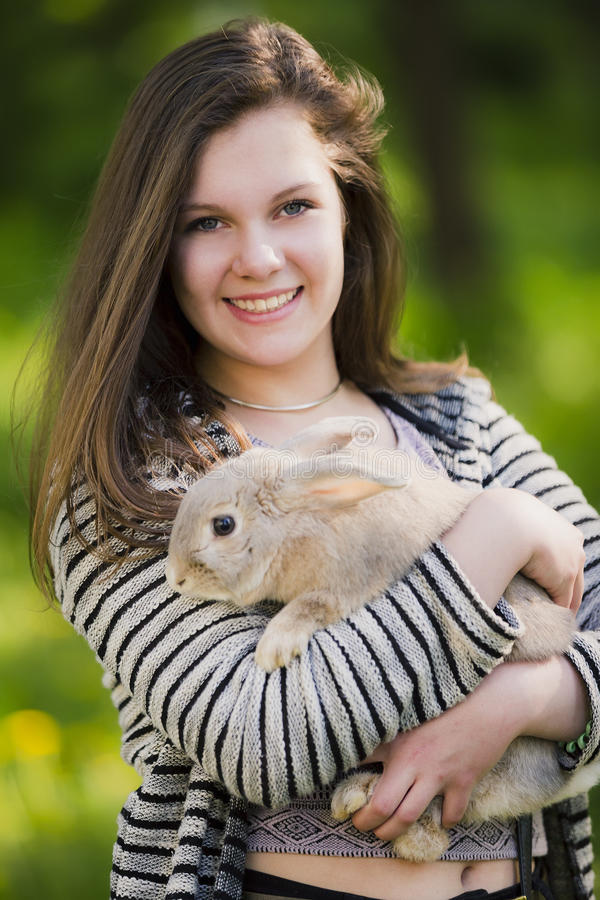 Happy young girl walking in spring, summer park with her bunny and smiling. Emotions of happiness. stock photography