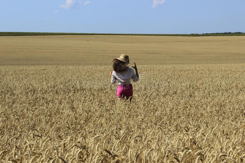 Happy young girl walking on a wheat meadow. stock photos