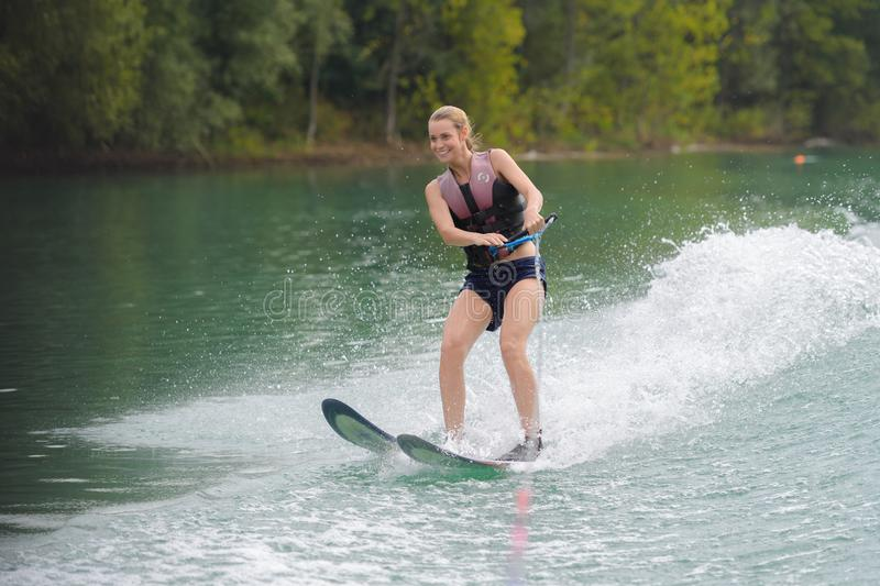 Happy young girl on water ski stock photo