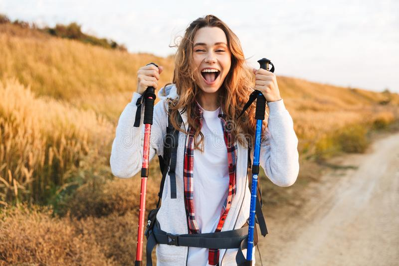Happy young girlcarrying backpack. Hiking stock image