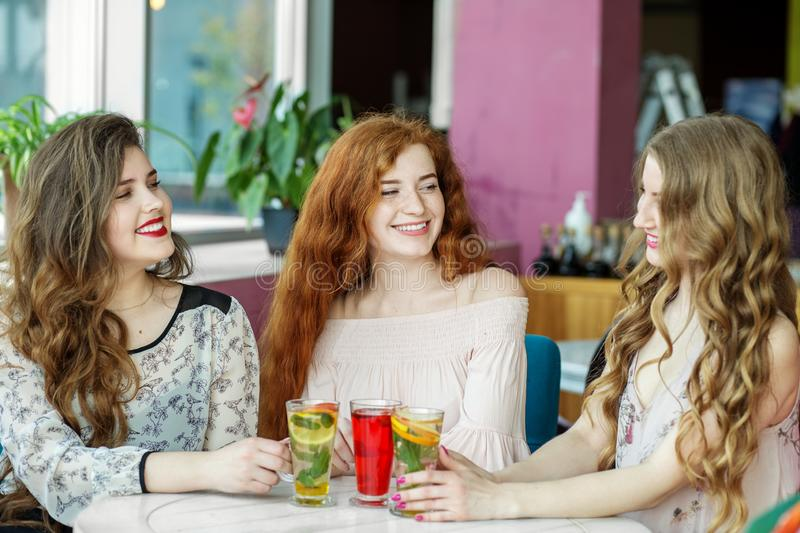 Happy young girls chatting in a cafe. Friendship, meeting and lifestyle concept stock photos