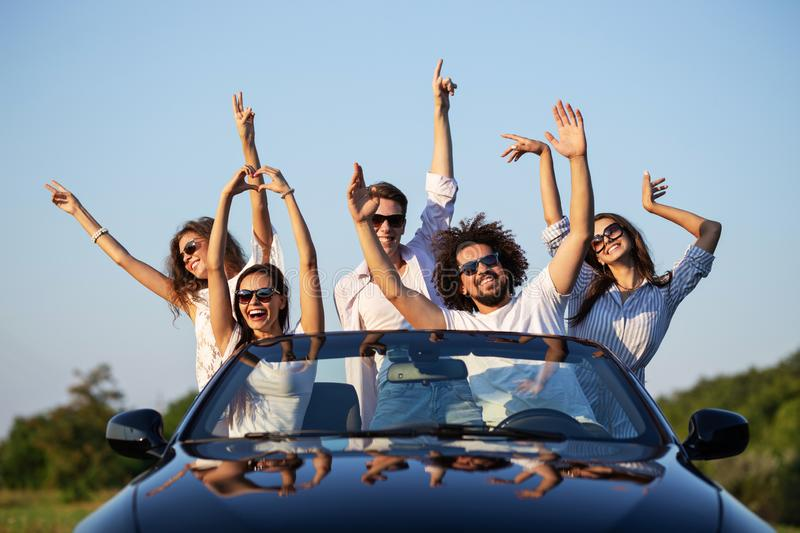 Happy young girls and guys in sunglasses are sitting in a black cabriolet on the road holding their hands up and smiling stock image