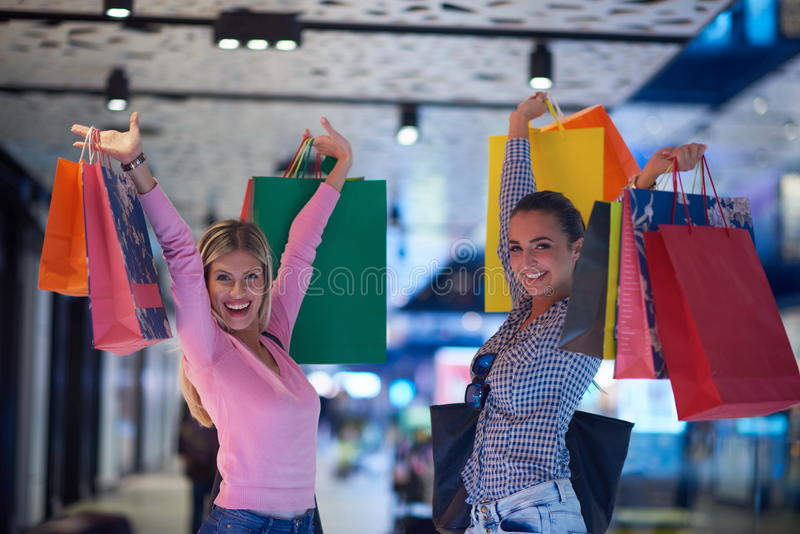 Happy young girls in shopping mall royalty free stock image