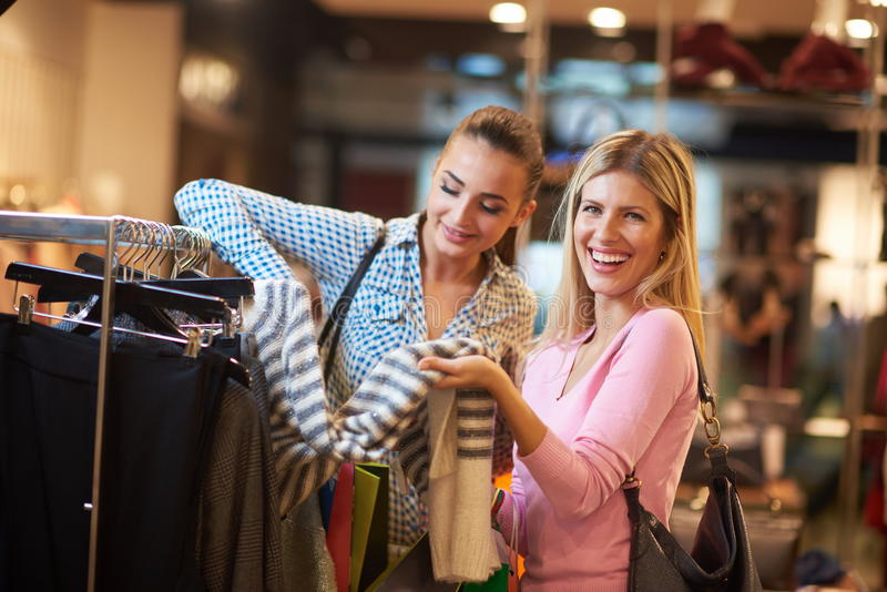 Happy young girls in shopping mall stock photos