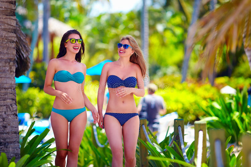 Happy young girls walking on tropical beach, during summer vacation stock images