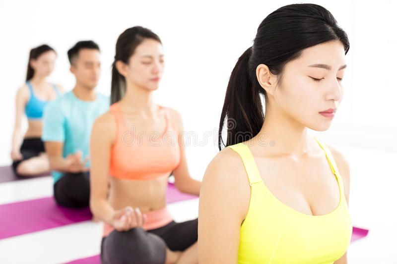 Happy young Group doing yoga exercises royalty free stock photo