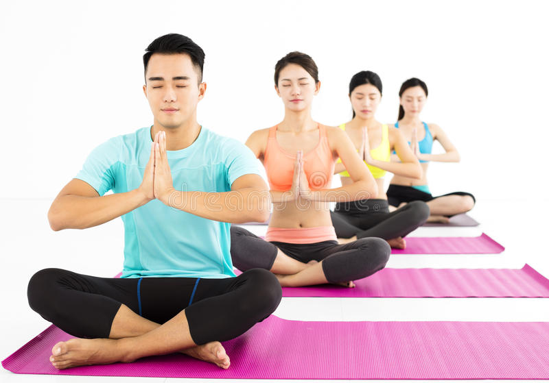 Happy young Group doing yoga exercises stock image