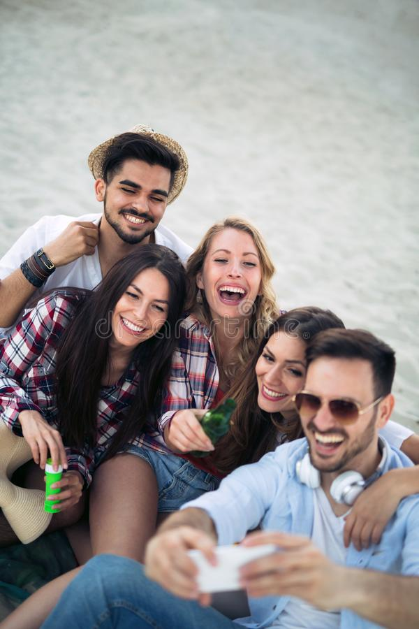 Happy young group of people taking selfies on beach royalty free stock photos