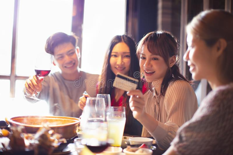 Young group showing credit card and chatting in restaurant stock photos