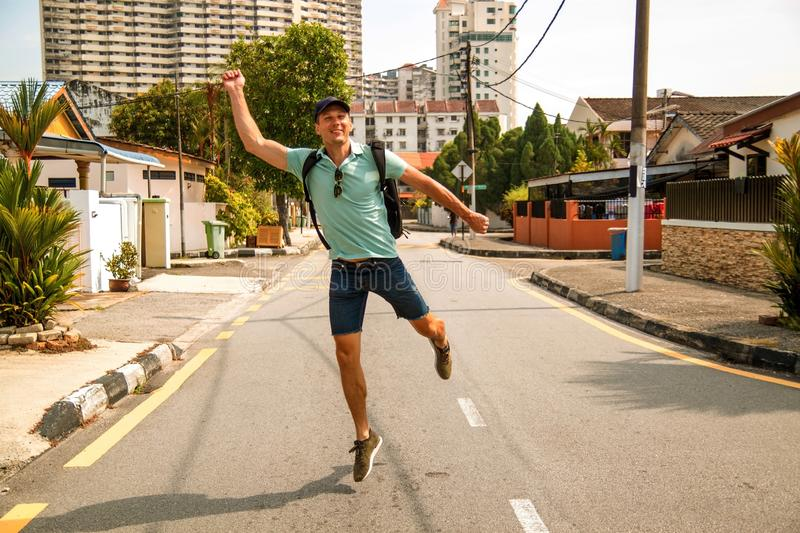 Young stylish man outdoors walking in the asian city . Happy young guy with backpack travels in asian city on sunny day royalty free stock photo