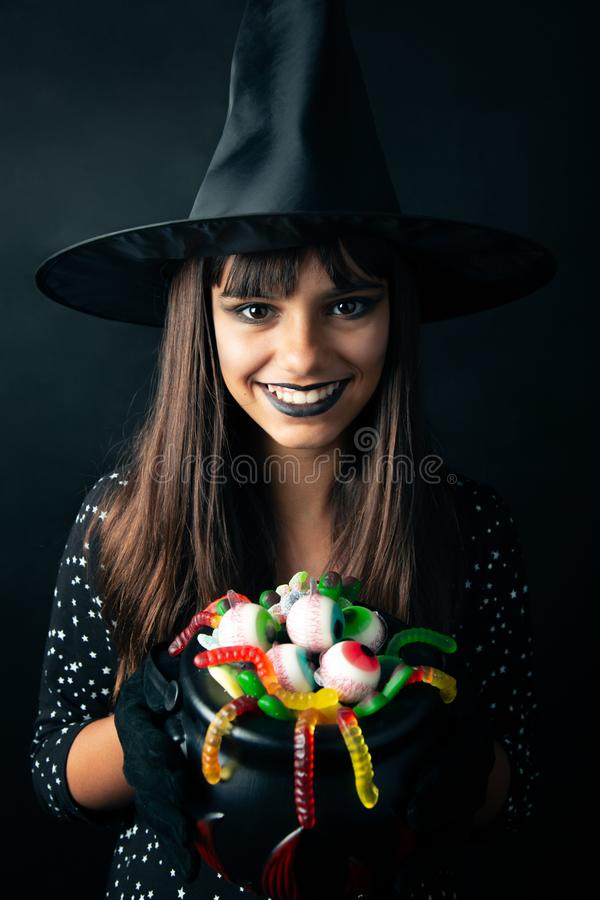 Happy young witch holding Halloween candies. Happy young Halloween witch holding a cauldron full of candies with shape of eyes, worms and fingers royalty free stock photo