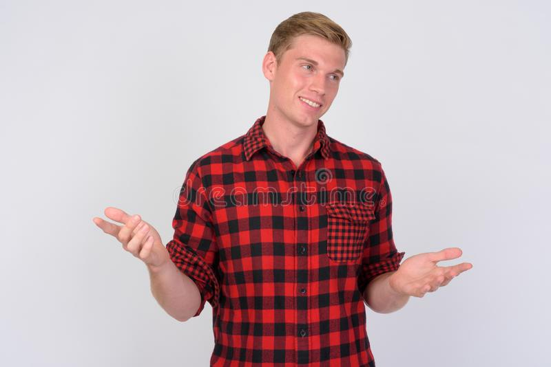 Happy young handsome hipster man with blond hair shrugging shoulders. Studio shot of young handsome hipster man with blond hair against white background stock photo
