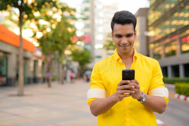 Happy young handsome Indian man using phone in the city street stock image