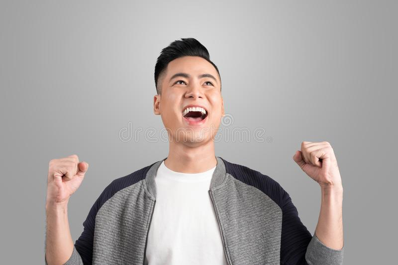 Happy young handsome man gesturing and keeping mouth open looking up royalty free stock photo