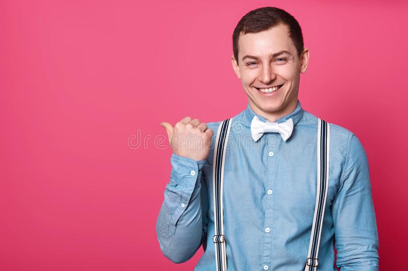 Happy young handsome man in shirt, suspenders and bow tie, points away with thumb finger and smiling while standing against pink royalty free stock images