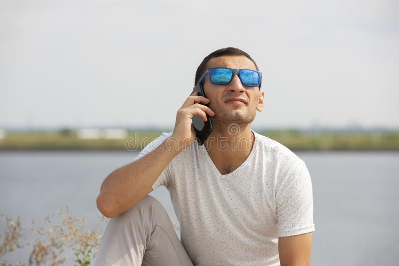 Happy young handsome man sitting on the bench outdoors and using smartphone stock photos
