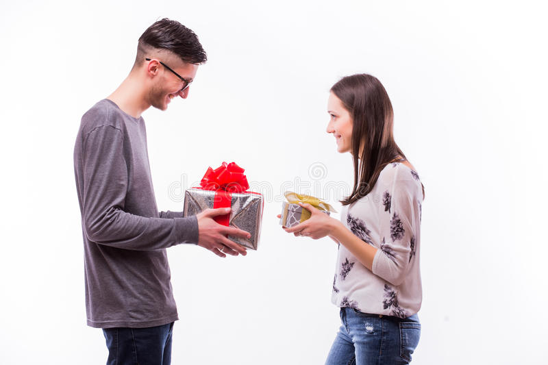 Happy young hipster couple change with present each other isolated on a white background. royalty free stock photo