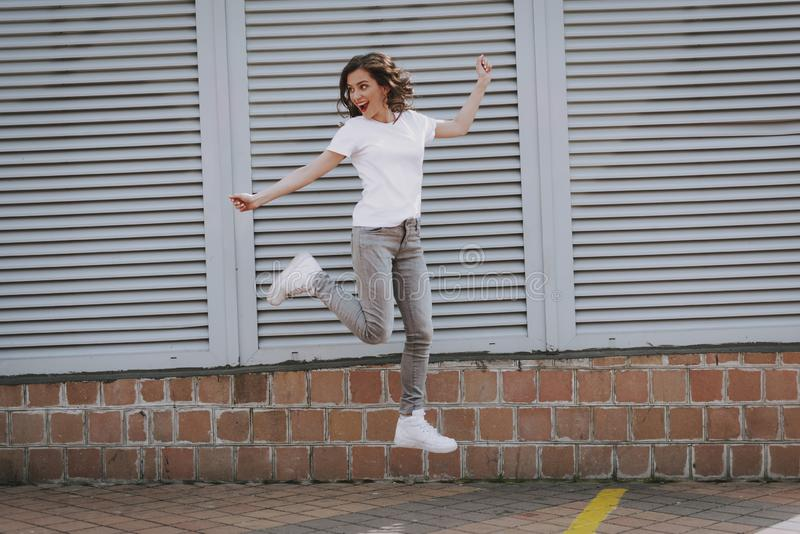 Happy young hipster girl jumping up on city view stock images