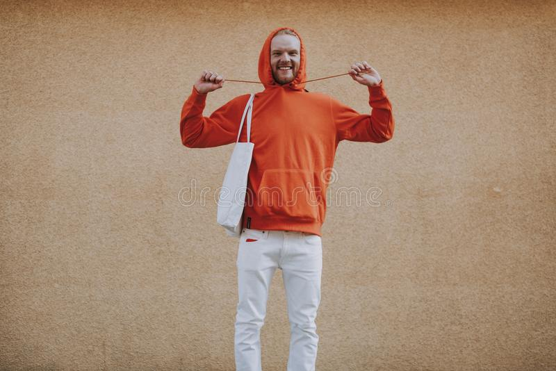 Happy young hipster man having fun on walk. Urban lifestyle concept. Front view portrait of young joyful hipster man in red fleece having fun with its hood laces stock image