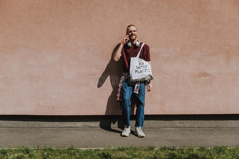 Happy young hipster man talking by mobile phone. Urban lifestyle and safe environment. Full length portrait of young smiling hipster guy with eco bag leaning on royalty free stock photos
