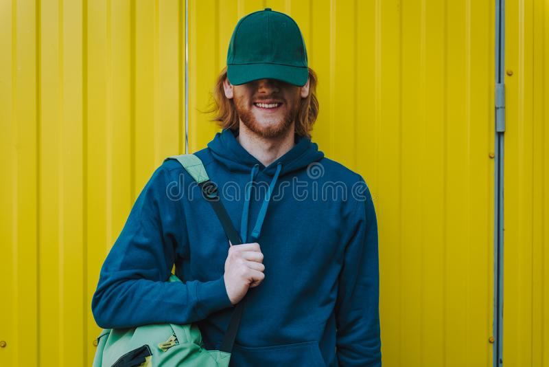 Happy young hipster man on yellow fence view royalty free stock photography