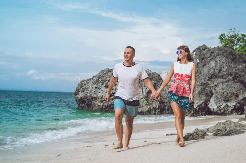Happy young honeymoon couple walking on the beach. Ocean, tropical vacation on Bali island, Indonesia. stock images